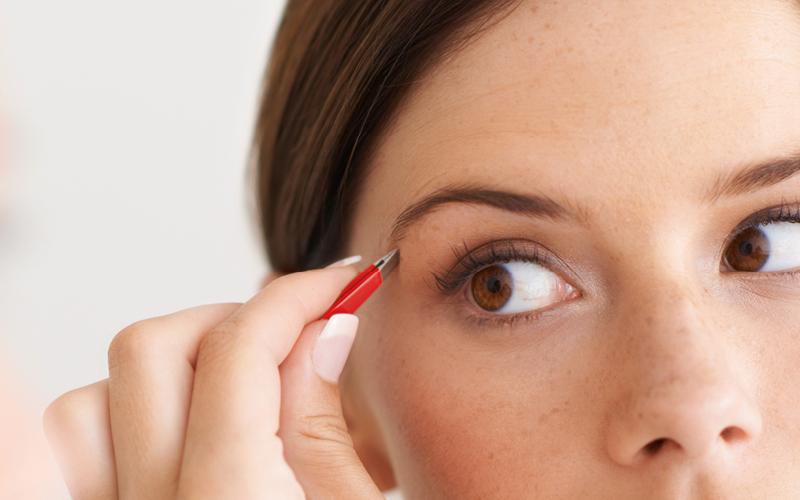 Frau zupft ihre Augenbrauen mit Pinzette von Erbe