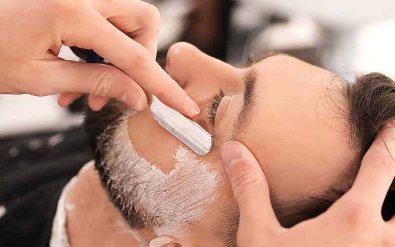 Mann wird rasiert mit Rasiernesser von Erbe